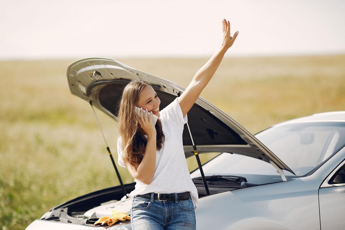 Kvinde der ringer efter vejhjælp ved sin nedbrudte bil og ser den ankomme