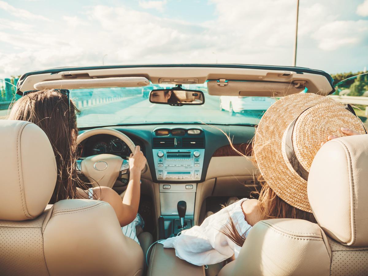 To kvinder der nyder deres nye åbne bil